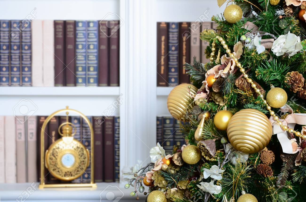 A Beautiful Decorated Christmas Tree On The Background Of Bookshelf With Many Books Different