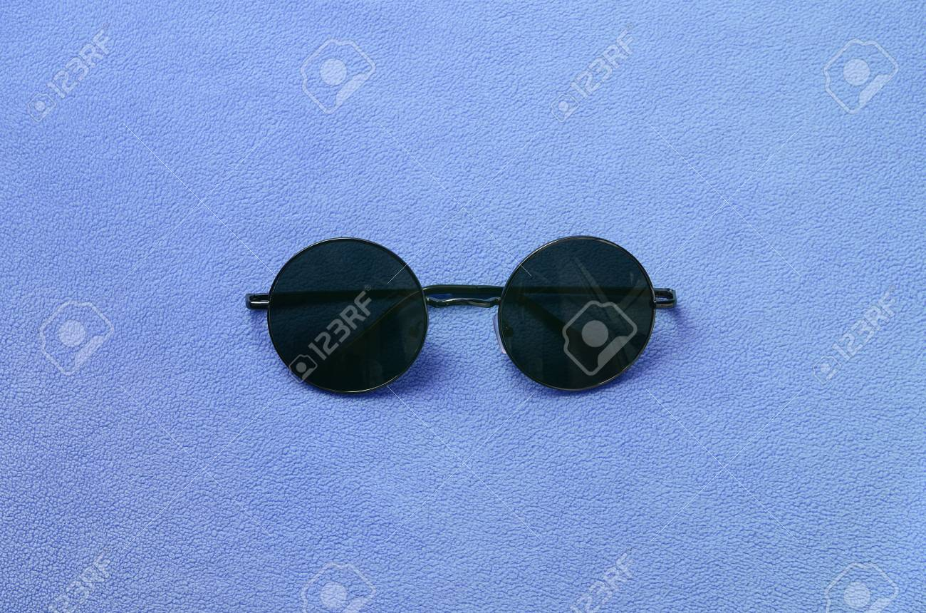 d6d7e52fd170 Stock Photo - Stylish black sunglasses with round glasses lies on a blanket  made of soft and fluffy light blue fleece fabric. Fashionable background  picture ...