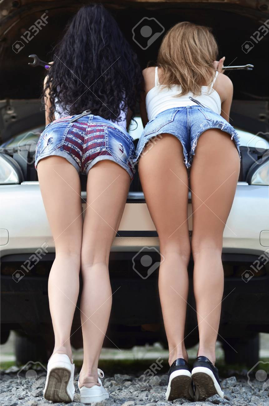 Rear view of two young girls in blue short denim shorts is repairing the car. two asses in shorts with wrenches in her back pockets near a silver car with open hood - 96247250