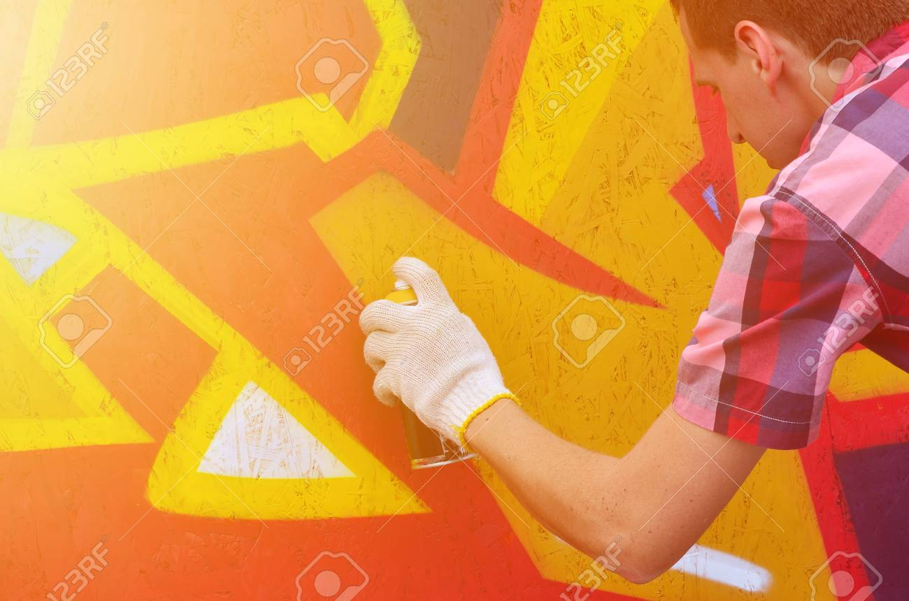 A Young Red-haired Graffiti Artist Paints A New Graffiti On The ...