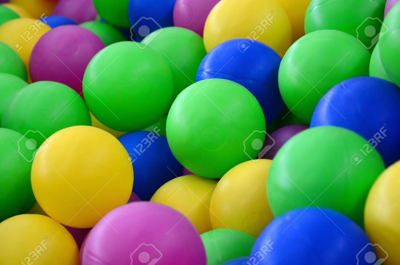 Colored plastic balls in pool of game room. Swimming pool for..