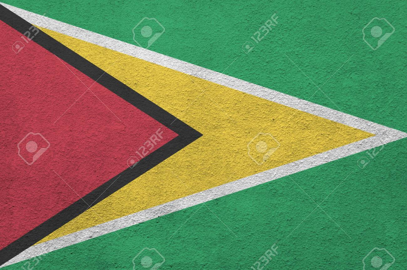Guyana flag depicted in bright paint colors on old relief plastering wall close up. Textured banner on rough background - 134975800
