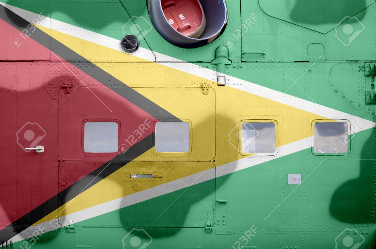 Guyana flag depicted on side part of military armored helicopter close up. Army forces aircraft conceptual background - 135239928