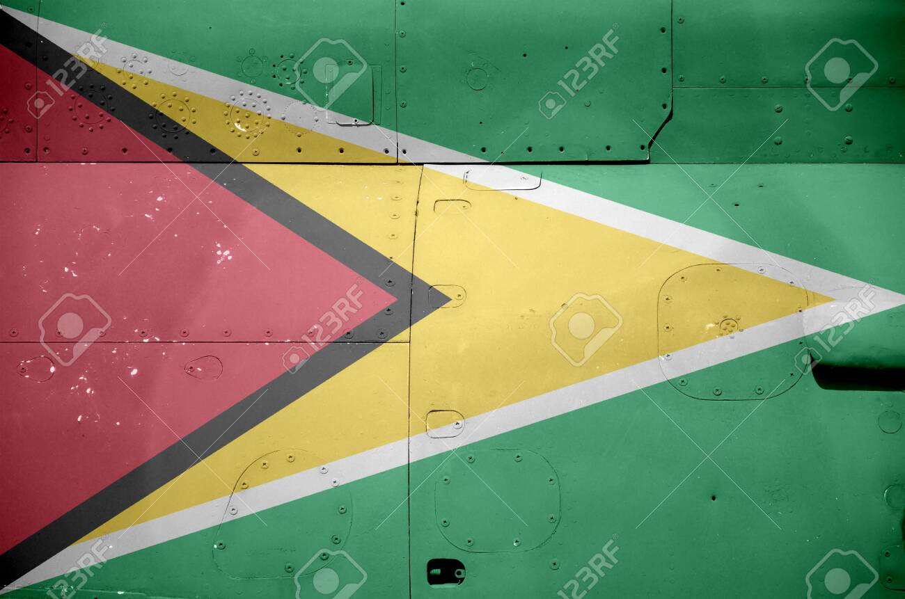 Guyana flag depicted on side part of military armored helicopter close up. Army forces aircraft conceptual background - 135240768