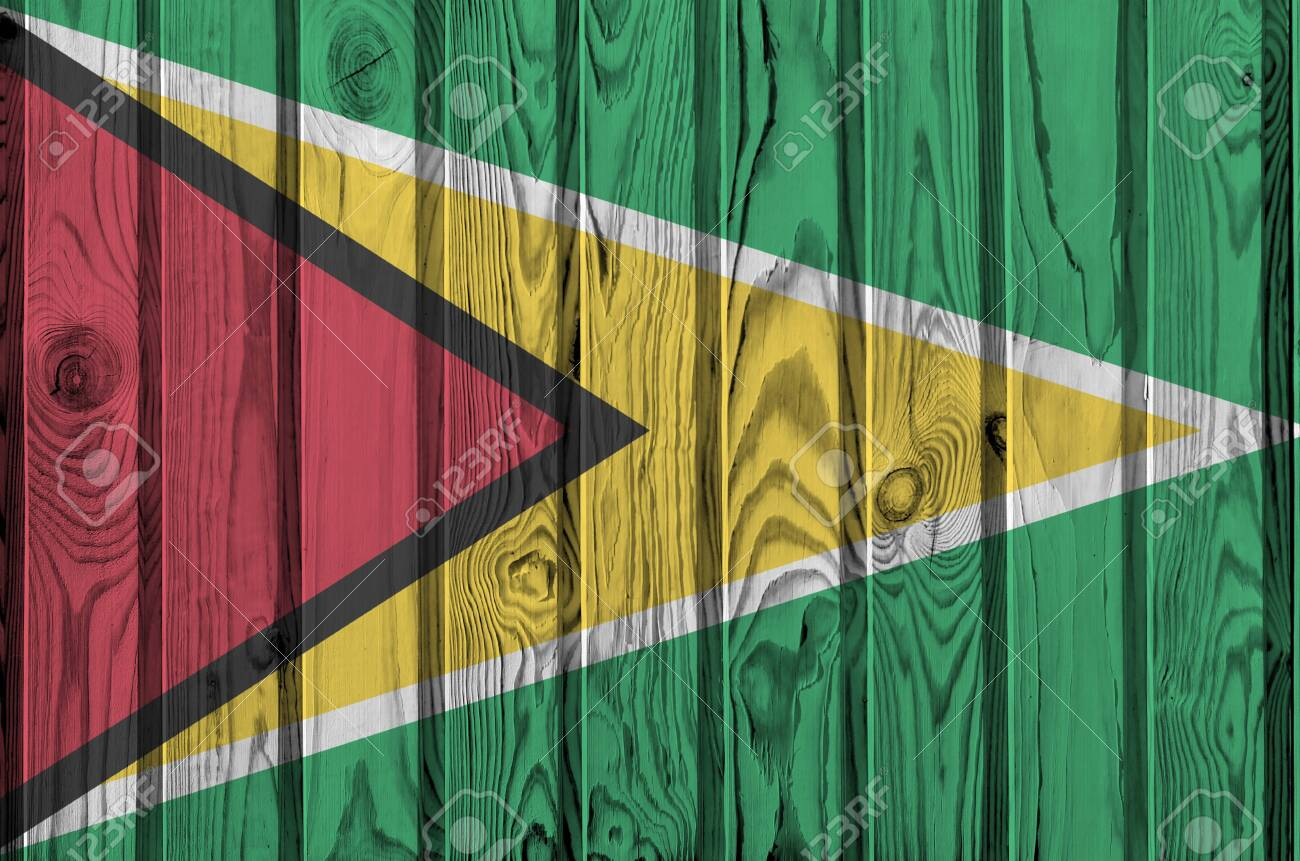 Guyana flag depicted in bright paint colors on old wooden wall close up. Textured banner on rough background - 135194251