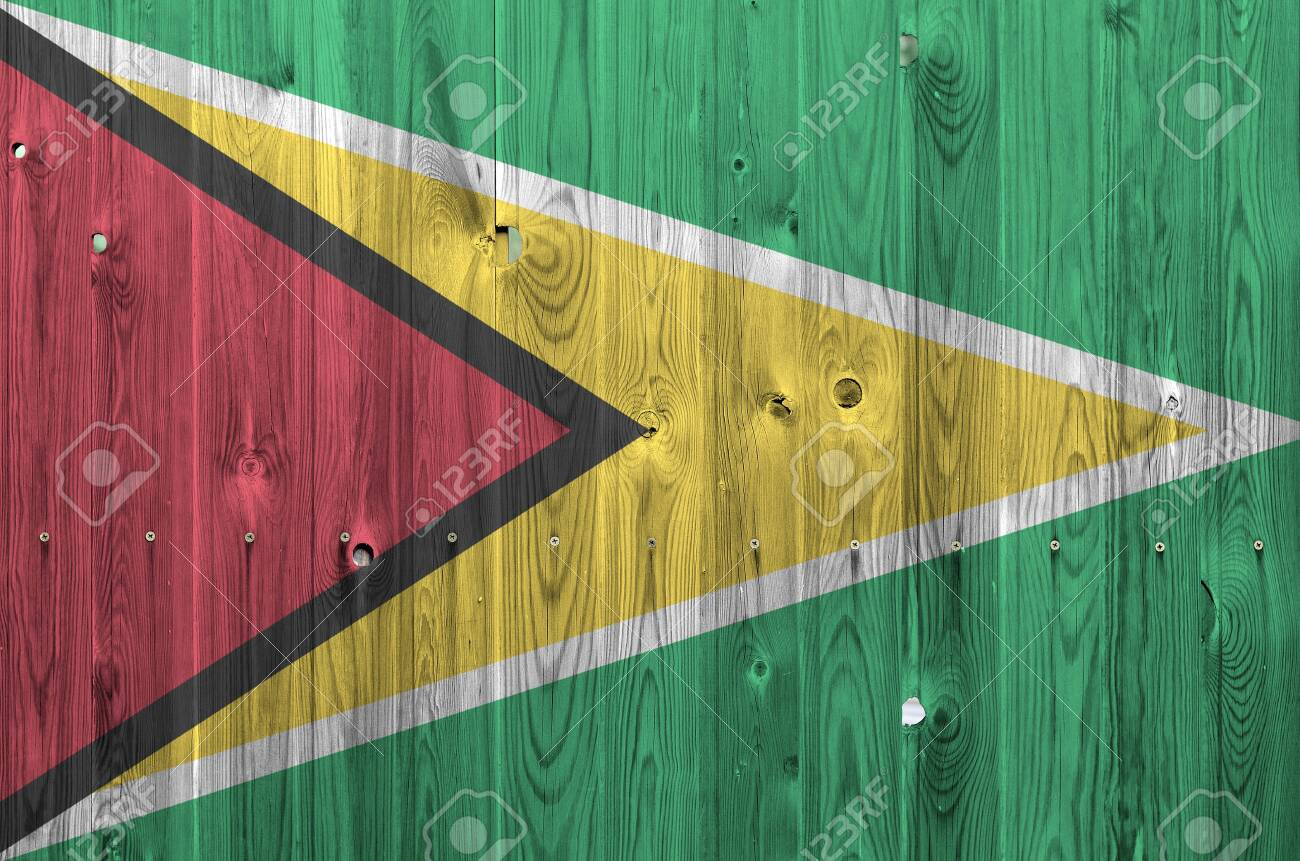 Guyana flag depicted in bright paint colors on old wooden wall close up. Textured banner on rough background - 135194582