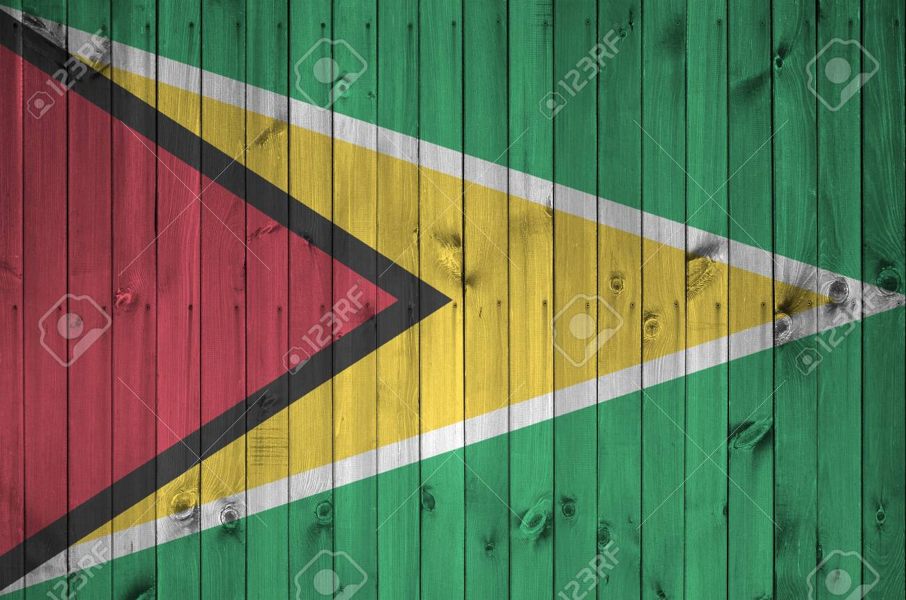 Guyana flag depicted in bright paint colors on old wooden wall close up. Textured banner on rough background - 135194576