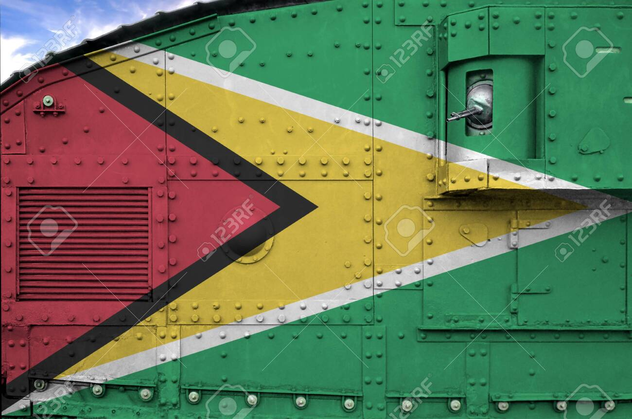 Guyana flag depicted on side part of military armored tank close up. Army forces conceptual background - 135360099