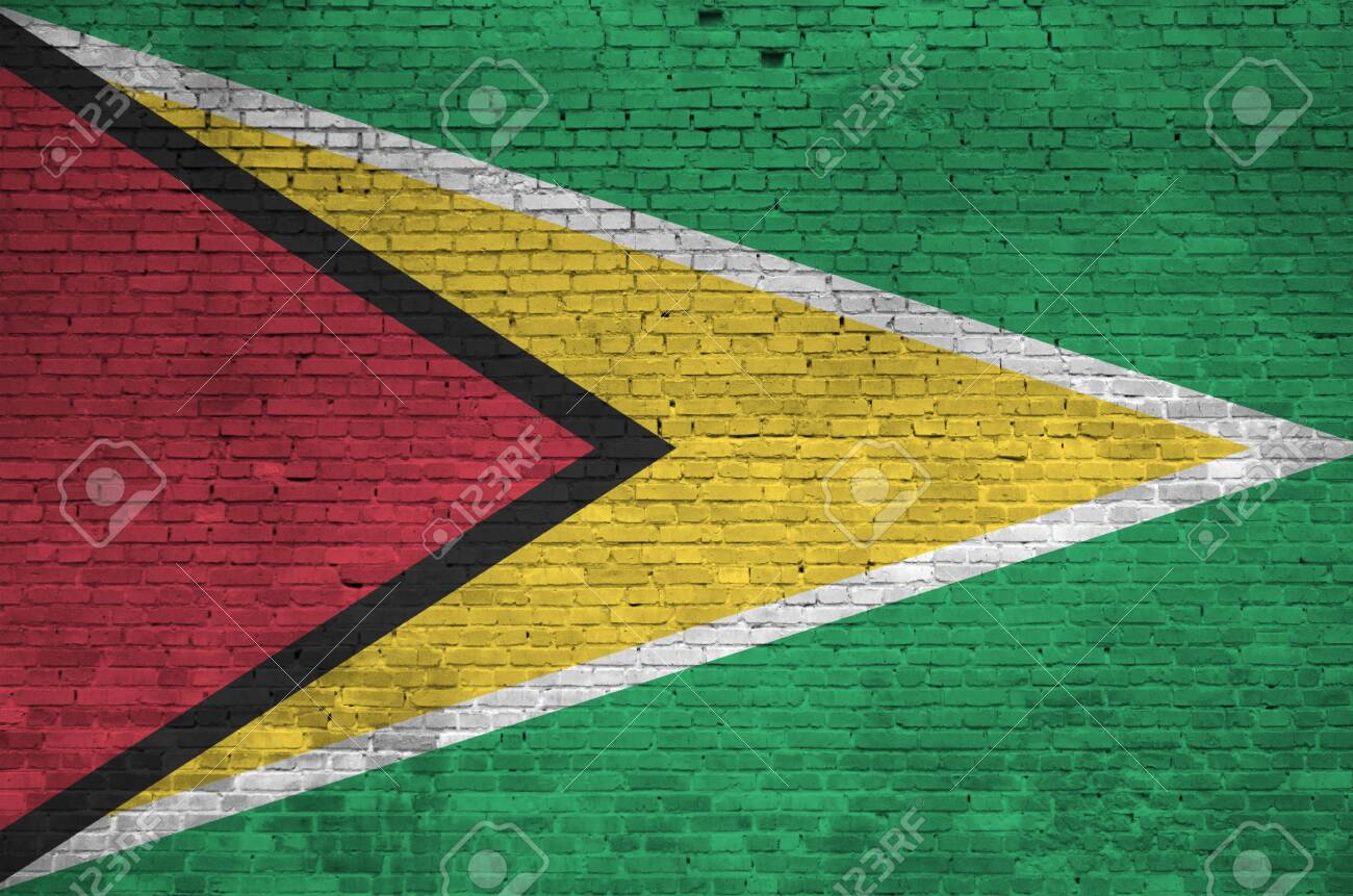 Guyana flag depicted in paint colors on old brick wall close up. Textured banner on big brick wall masonry background - 135197125
