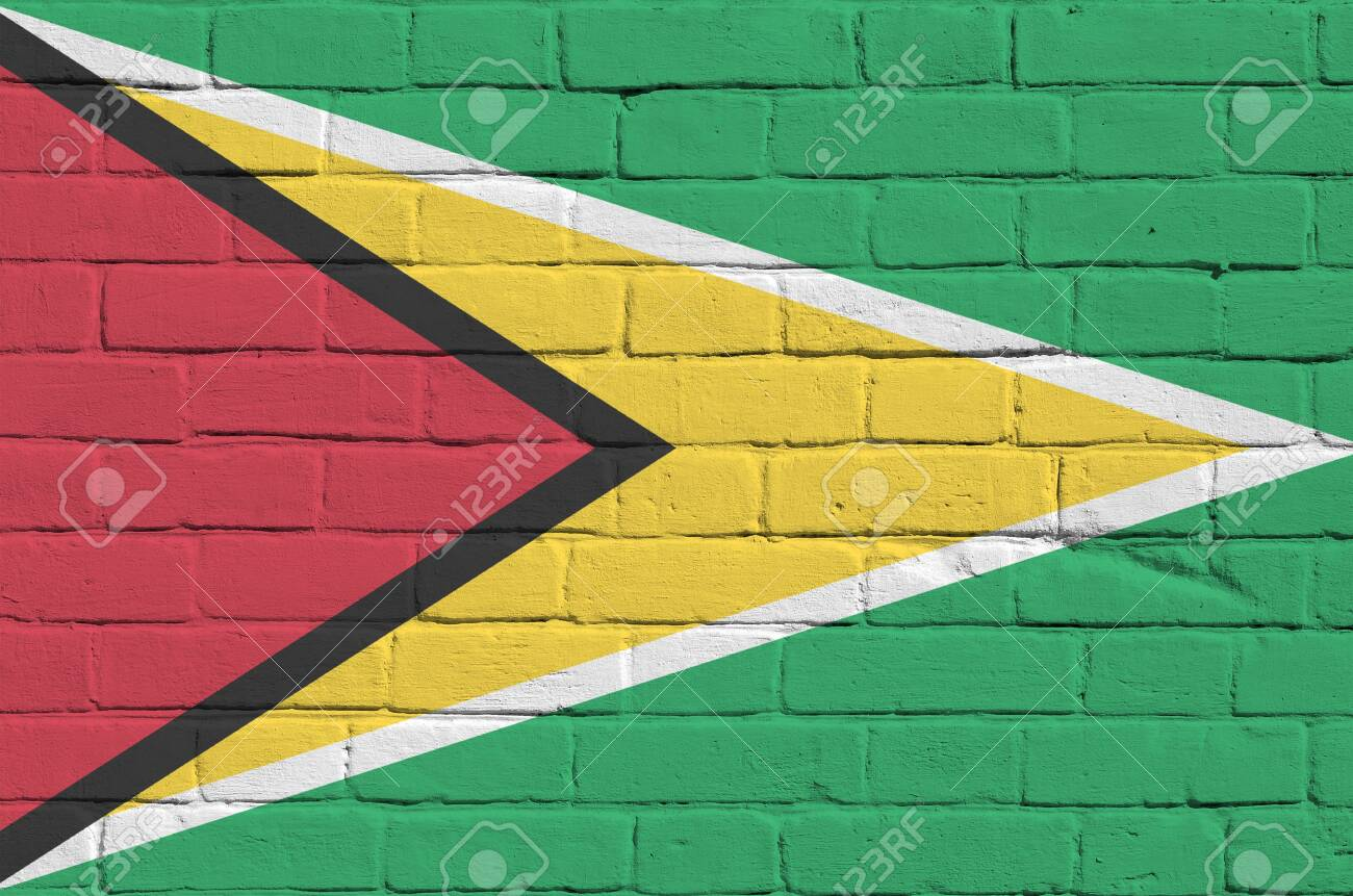 Guyana flag depicted in paint colors on old brick wall close up. Textured banner on big brick wall masonry background - 135197900