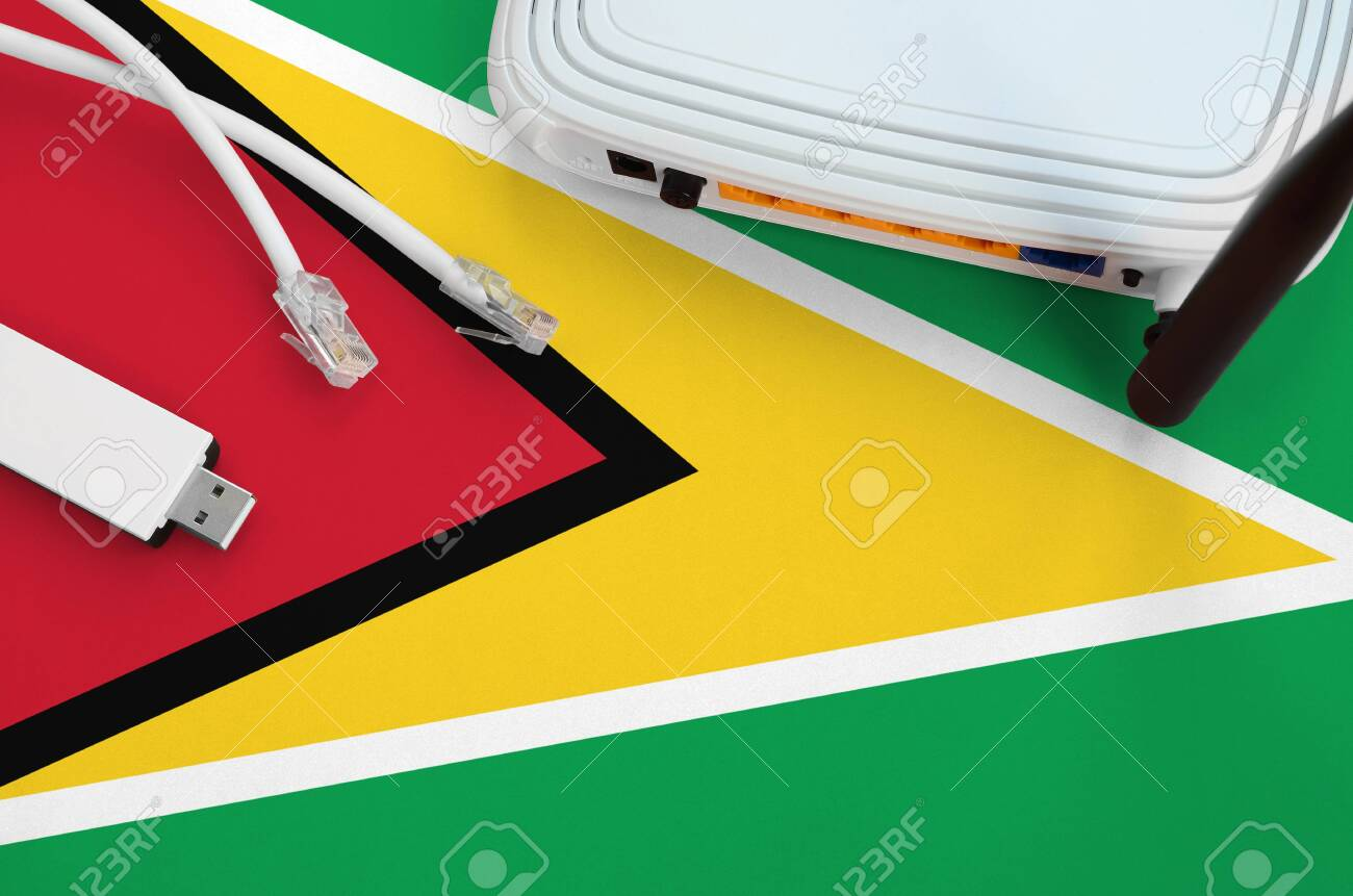 Guyana flag depicted on table with internet rj45 cable, wireless usb wifi adapter and router. Internet connection concept - 135374309
