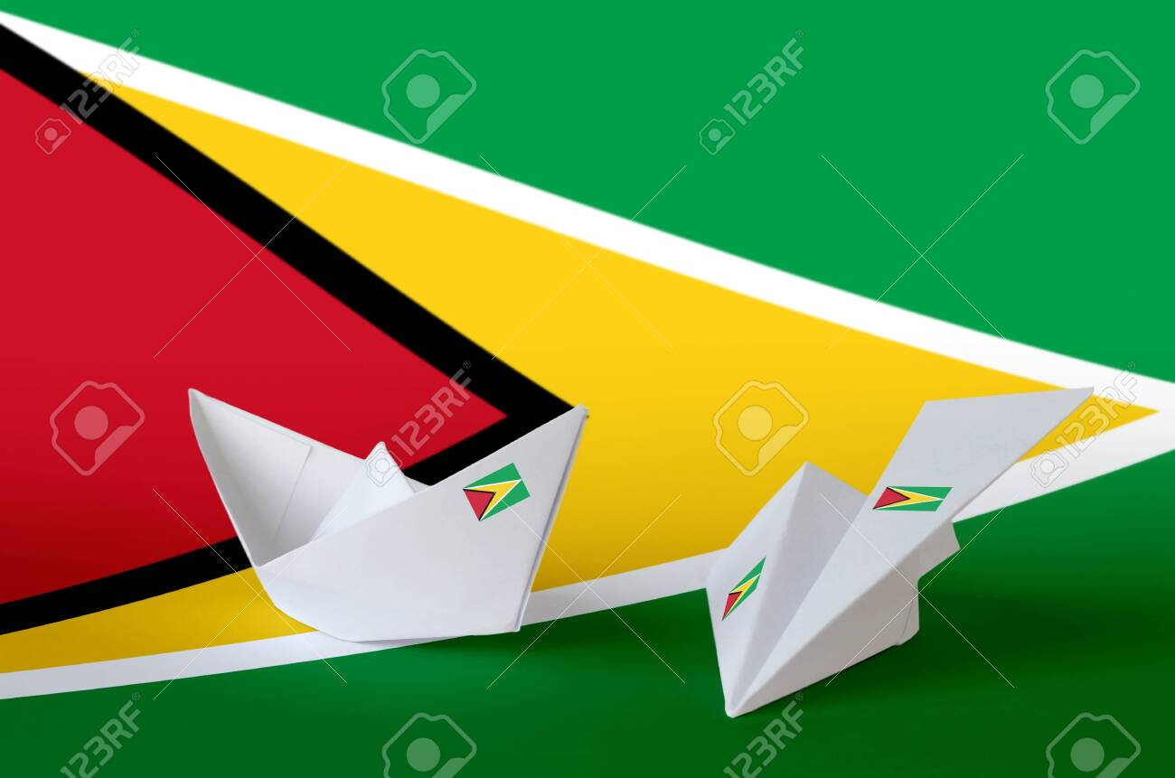 Guyana flag depicted on paper origami airplane and boat. Oriental handmade arts concept - 135199881