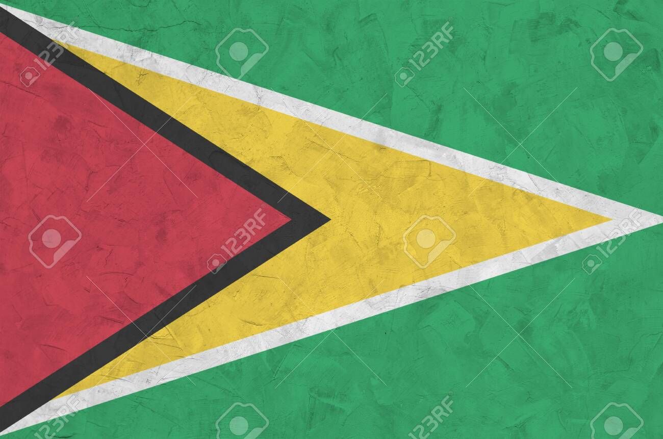 Guyana flag depicted in bright paint colors on old relief plastering wall close up. Textured banner on rough background - 135358571
