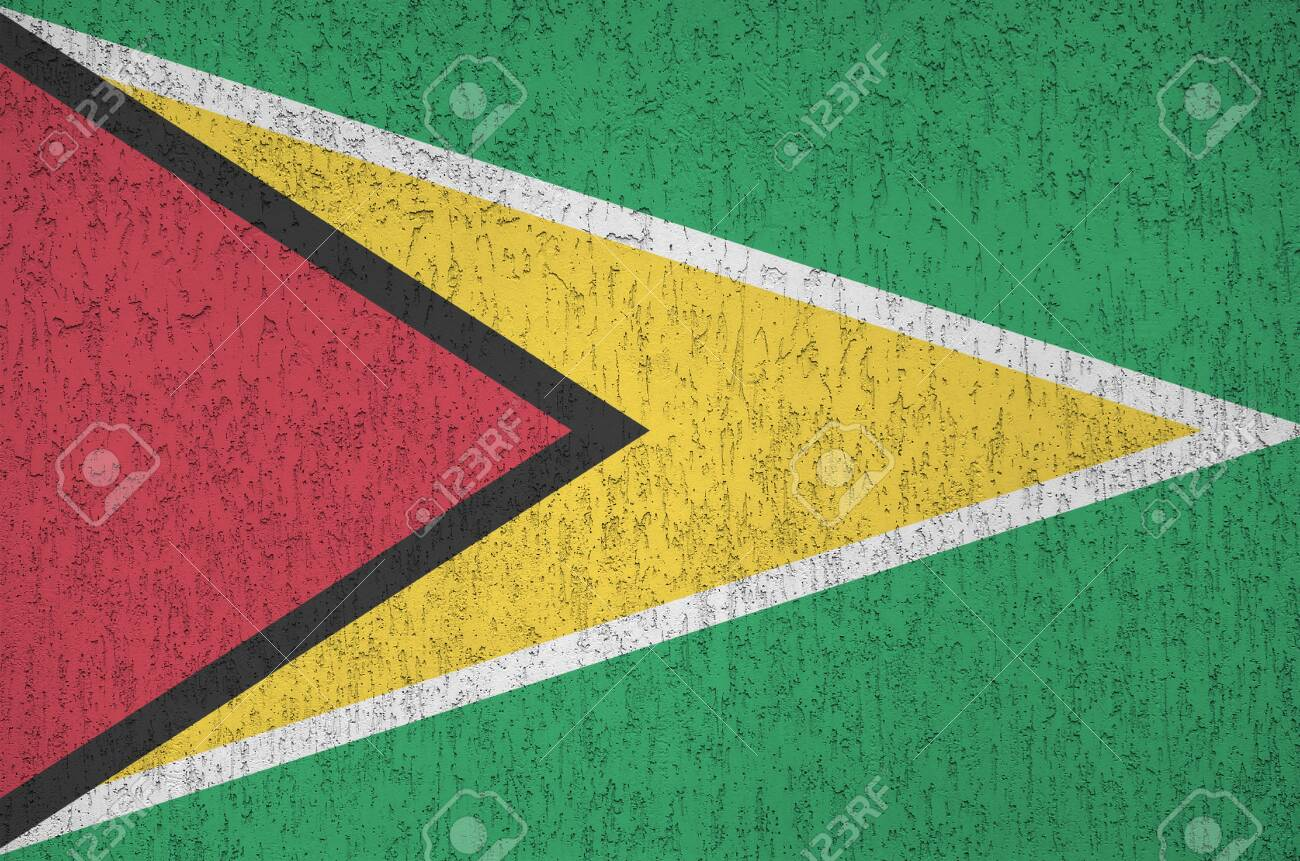 Guyana flag depicted in bright paint colors on old relief plastering wall close up. Textured banner on rough background - 135389783