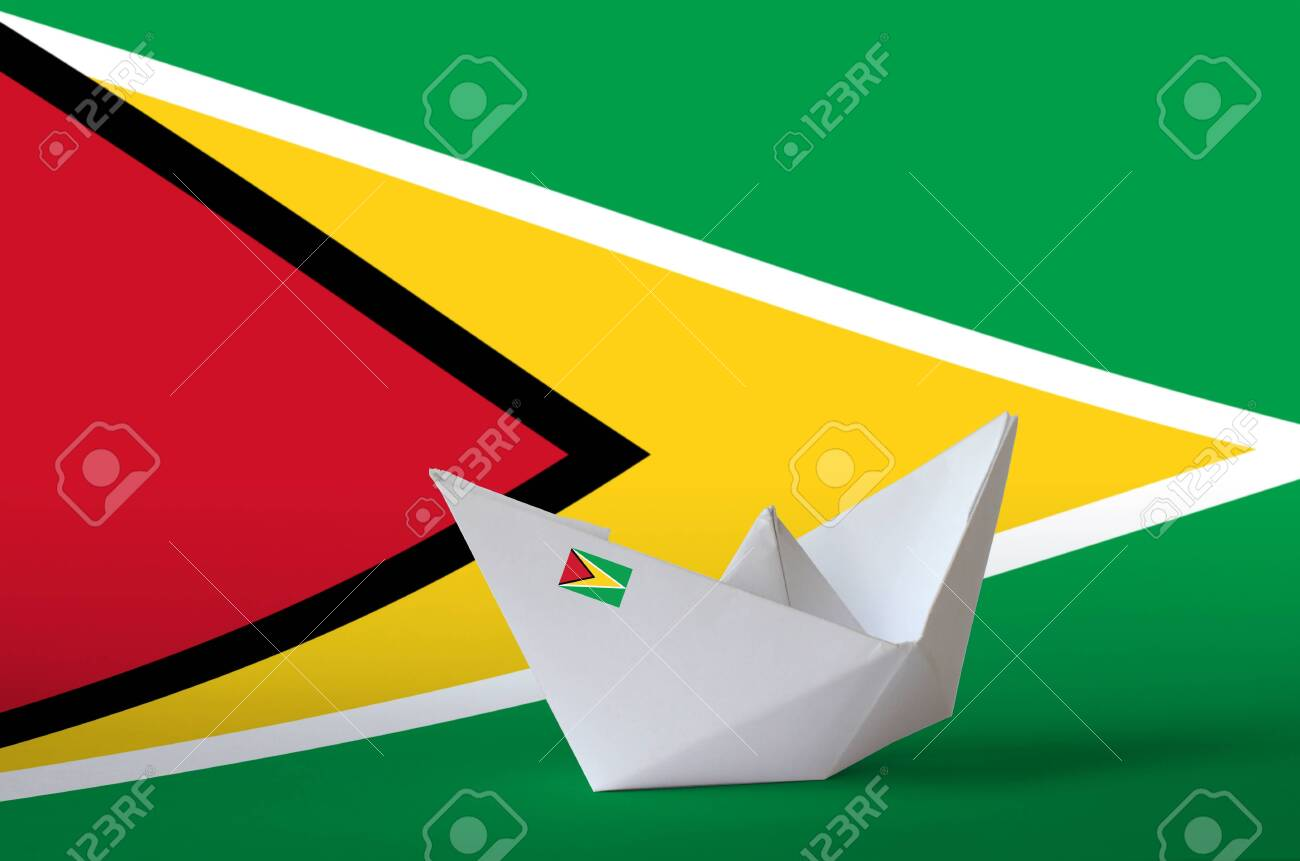 Guyana flag depicted on paper origami ship closeup. Oriental handmade arts concept - 135200129