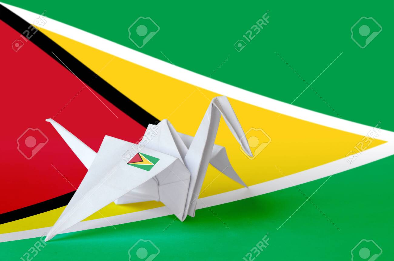 Guyana flag depicted on paper origami crane wing. Oriental handmade arts concept - 135392102