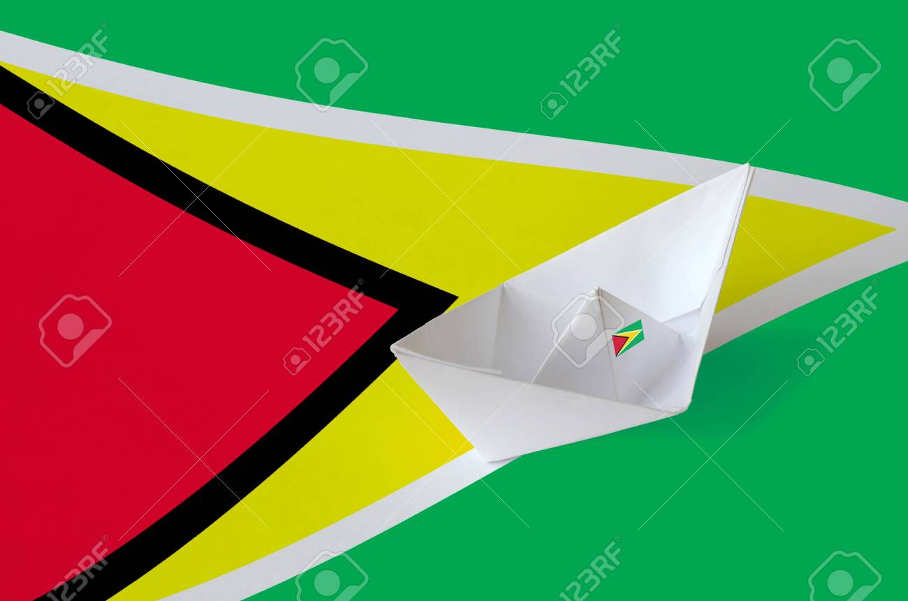 Guyana flag depicted on paper origami ship closeup. Oriental handmade arts concept - 135200275