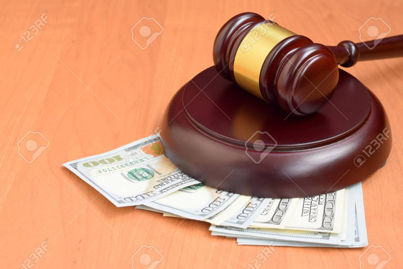 Judge gavel and money on brown wooden table. Many hundred dollar bills under judge malice on court desk. Judgement and bribe concept - 143798172
