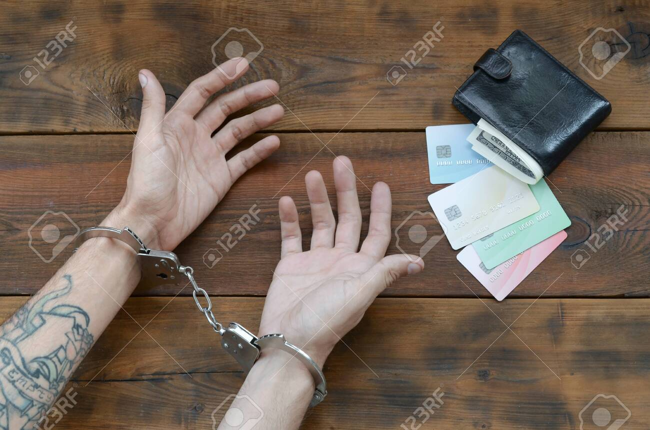 Cuffed hands of tattooed criminal suspect of carding and fake credit cards with cash in purse as evidence for investigation. Above view to old prison wooden table - 145516650
