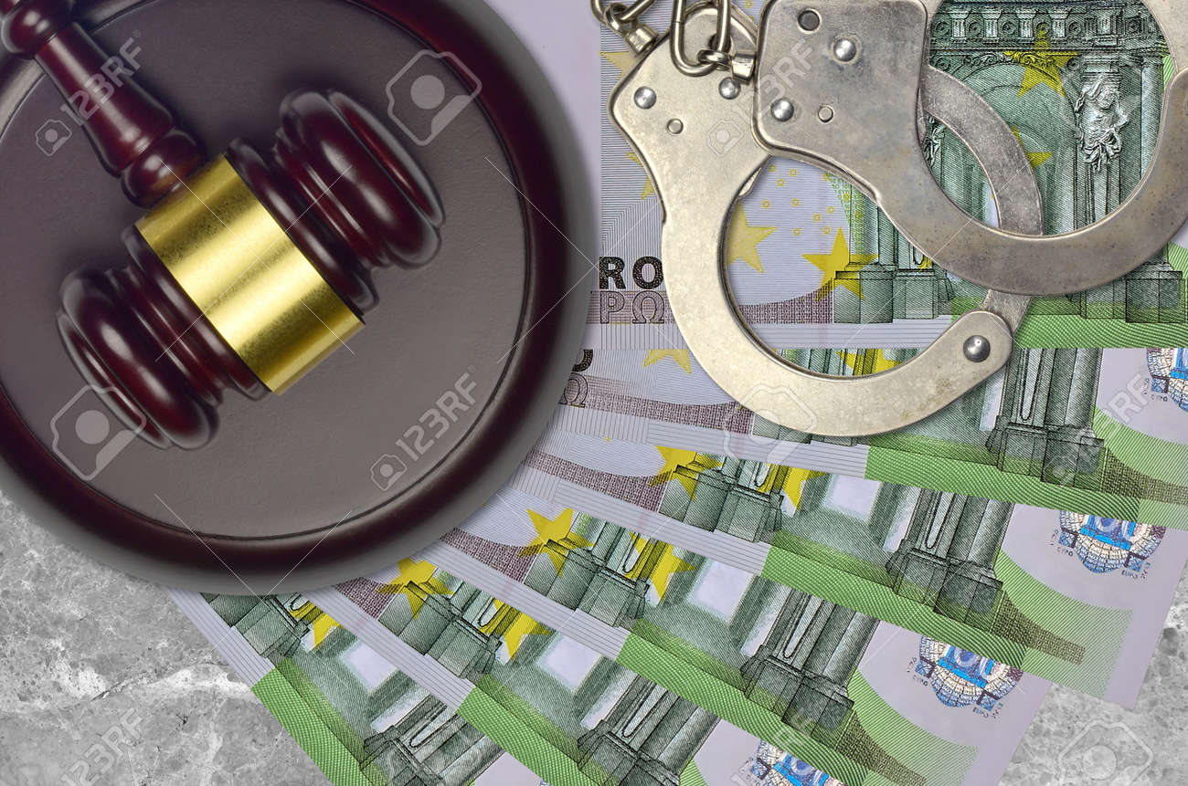 100 Euro bills and judge hammer with police handcuffs on court desk. Concept of judicial trial or bribery. Tax avoidance or tax evasion - 157251430