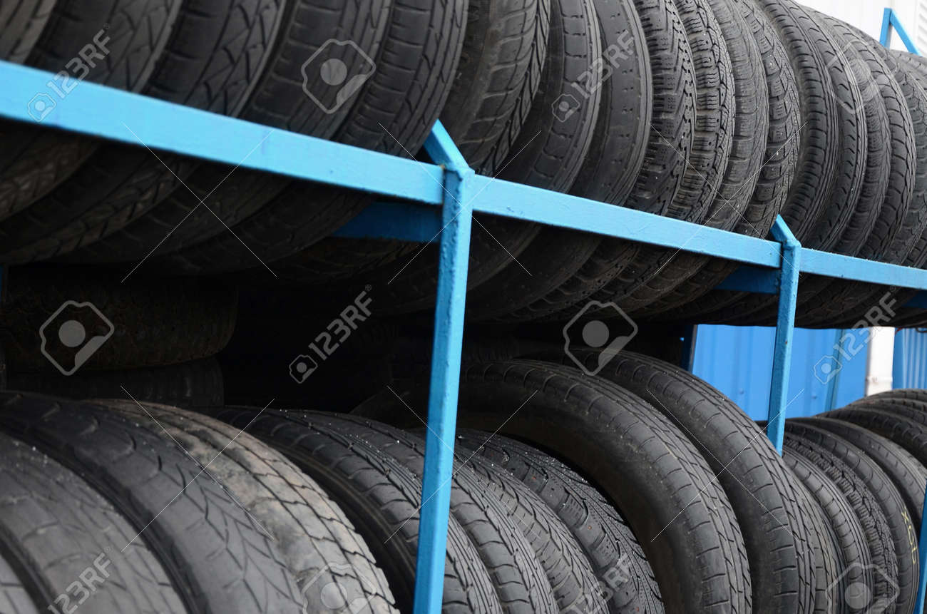 Rack with variety of car tires in automobile store. Many black tires. Tire stack background. Selective focus - 159116077