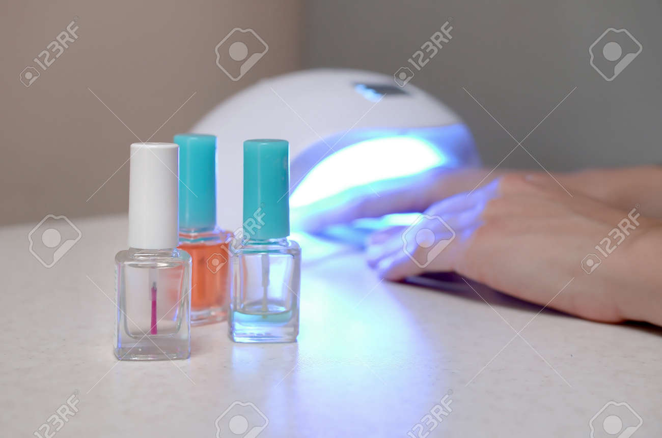 Three colorless transparent nail polish bottles in background of female hands in gel uv led nail white lamp for drying manicure. Beauty care women procedures in salon or home on gray background - 167449954