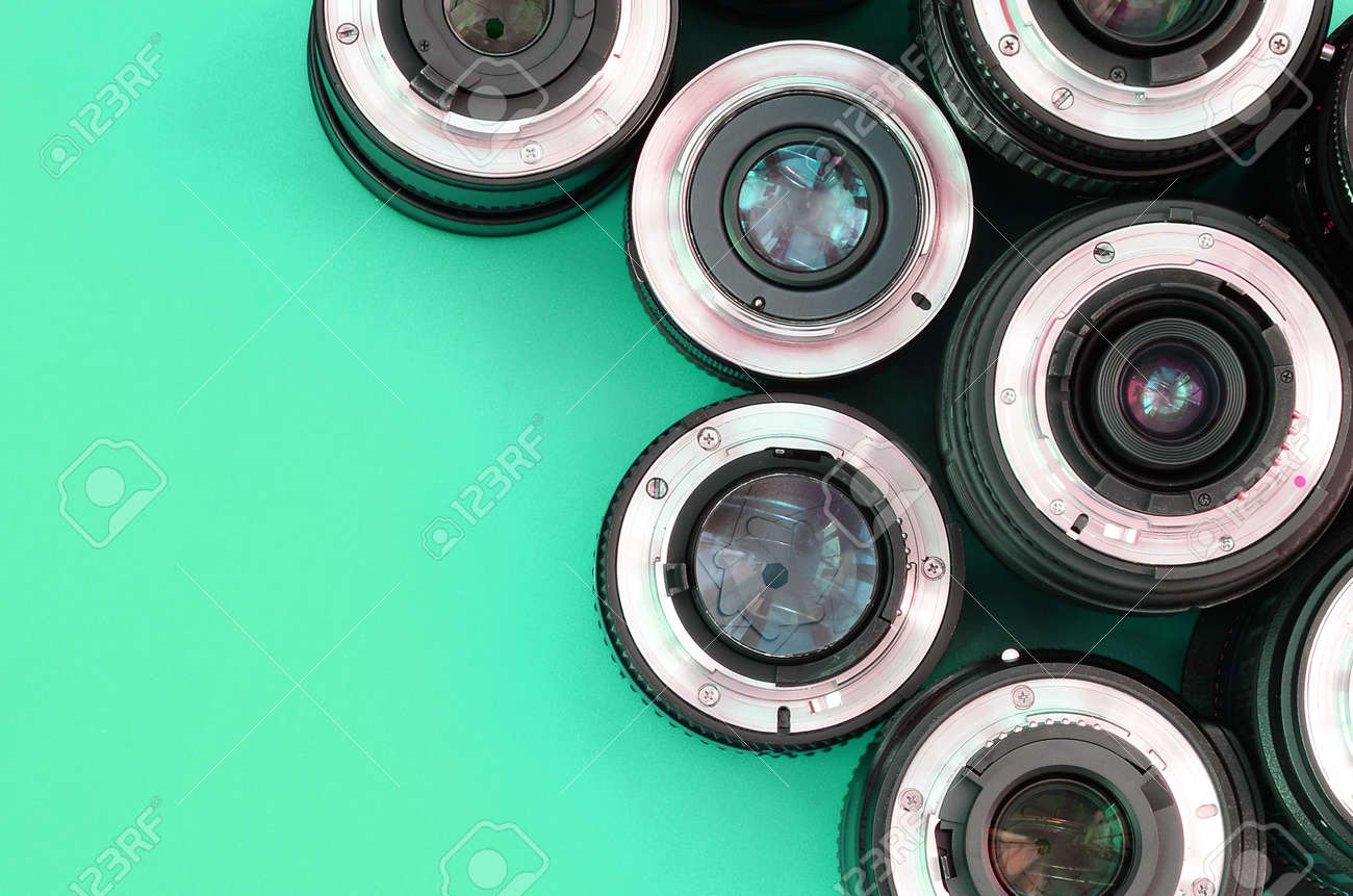 Several photographic lenses lie on a bright turquoise background. Space for text - 167450070