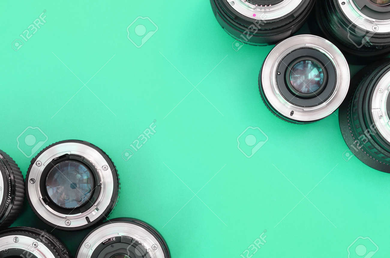 Several photographic lenses lie on a bright turquoise background. Space for text - 167450148