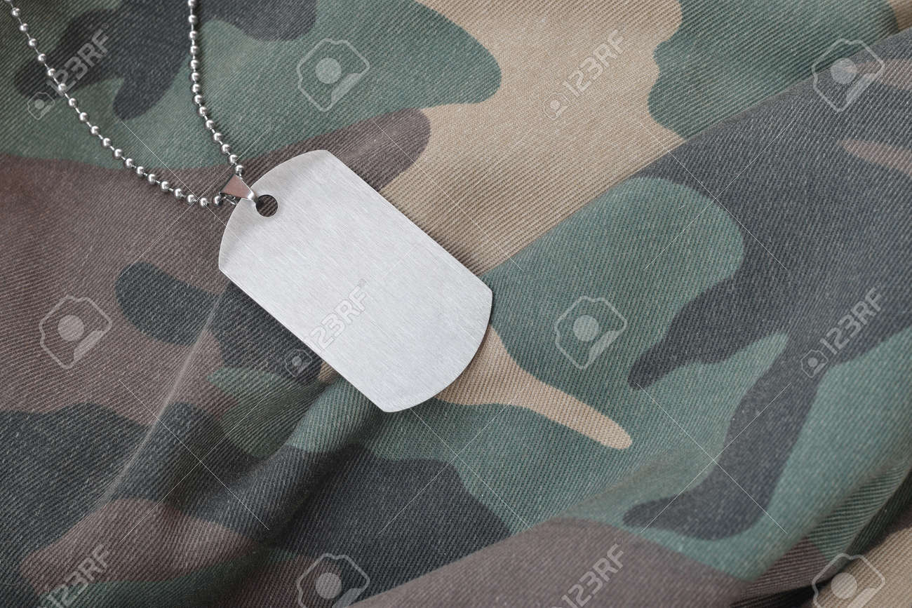 Silvery military beads with dog tag on camouflage fatigue uniform. Army token on soldiers camo jacket rear part - 167450165