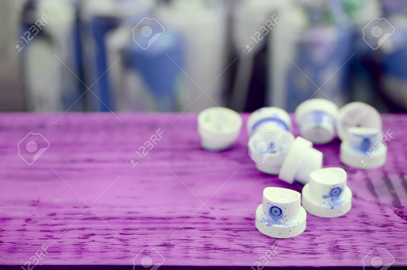 The soiled blue nozzles from the paint sprayer lies on a purple plank on a background of a many dirty spray cans for graffiti painting - 167450173