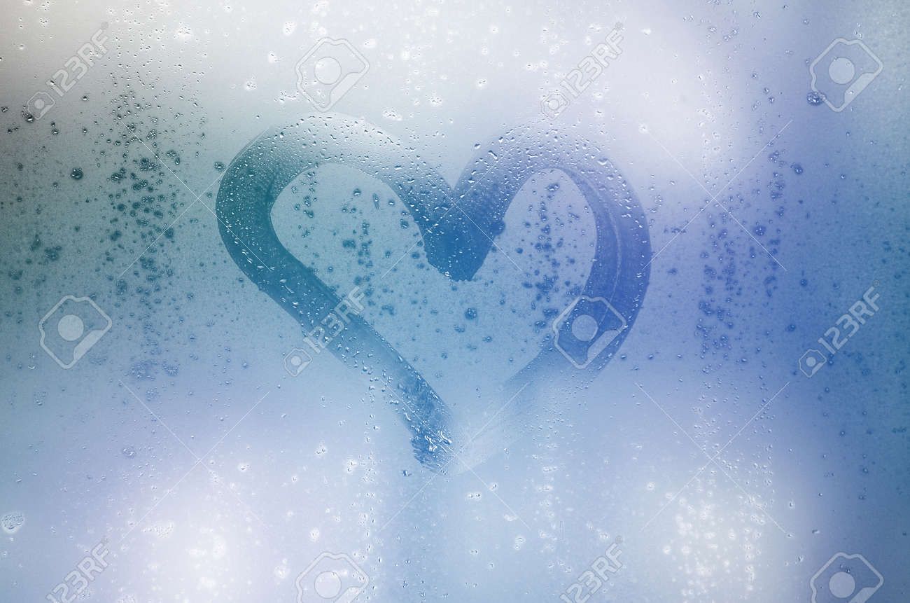 The heart is painted on the misted glass in the winter - 167450284