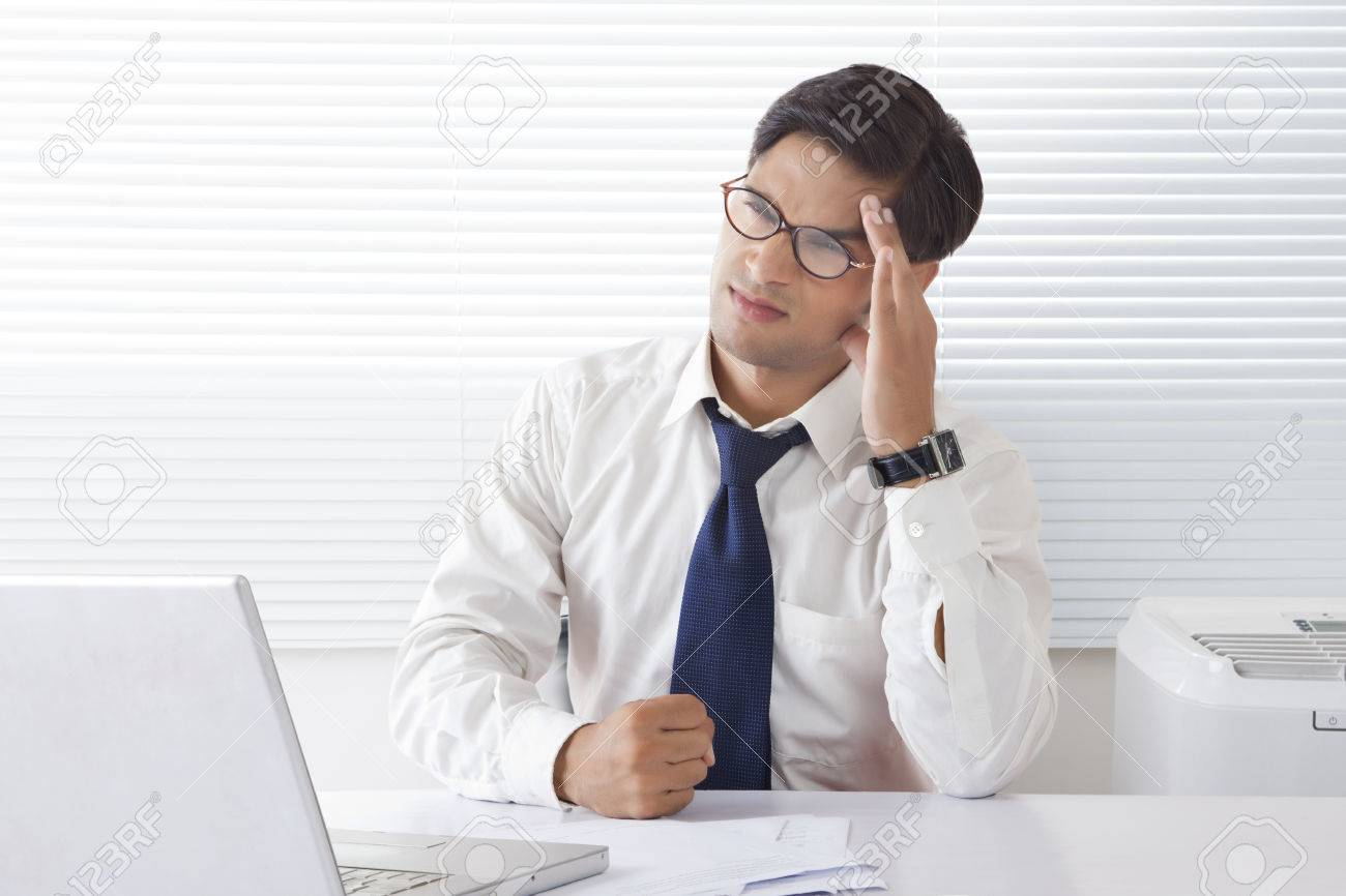Frustrated office worker on the phone holding stock photo image - Young Man Looking Frustrated And Angry Holding Forehead Sitting At Office Desk Stock Photo 80777956