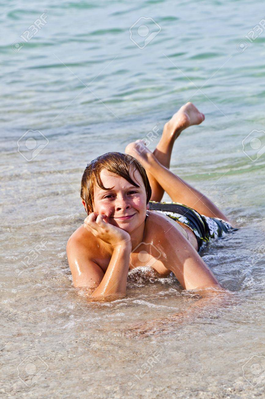 young boy enjoys lying at the beach in the surf Stock Photo - 9223482