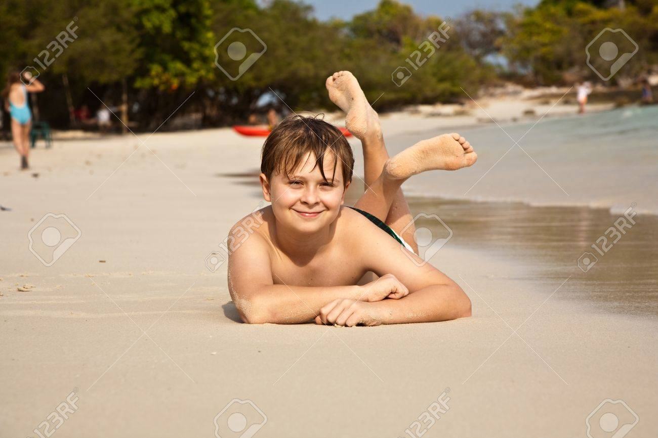 boy iy lying at the beach and enjoying the warmness of the water and looking self confident and happy Stock Photo - 9221449