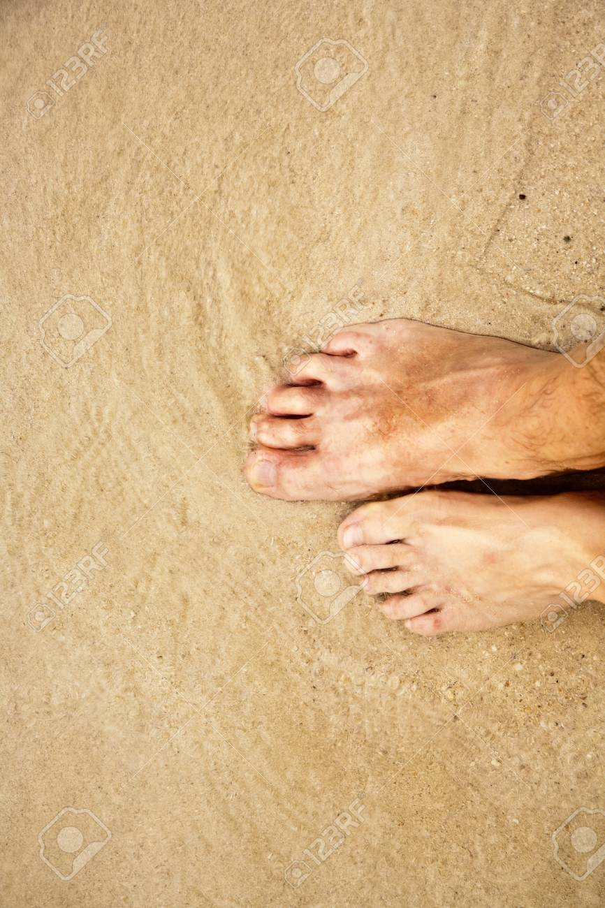 feet of a man in the fine sand surrounded by saltwater Stock Photo - 9348736