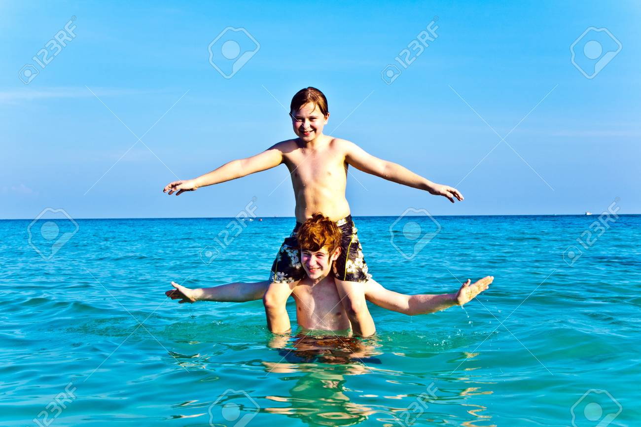 brothers are enjoying the clear warm water at the beautiful beach and playing pickaback Stock Photo - 9849959