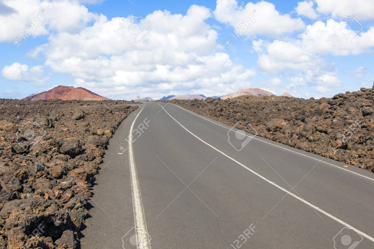 Road through lava rocks and volcanic mountains. Los Hervideros. Lanzarote Stock Photo - 13369877