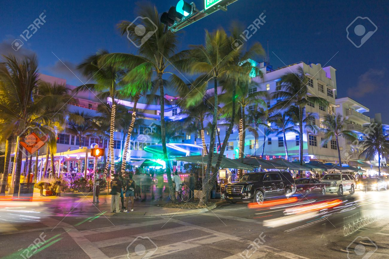 MIAMI, USA - AUG 23, 2014: Palm trees and art deco hotels at Ocean Drive by night. The road is the main thoroughfare through South Beach in Miami, USA. - 32895691