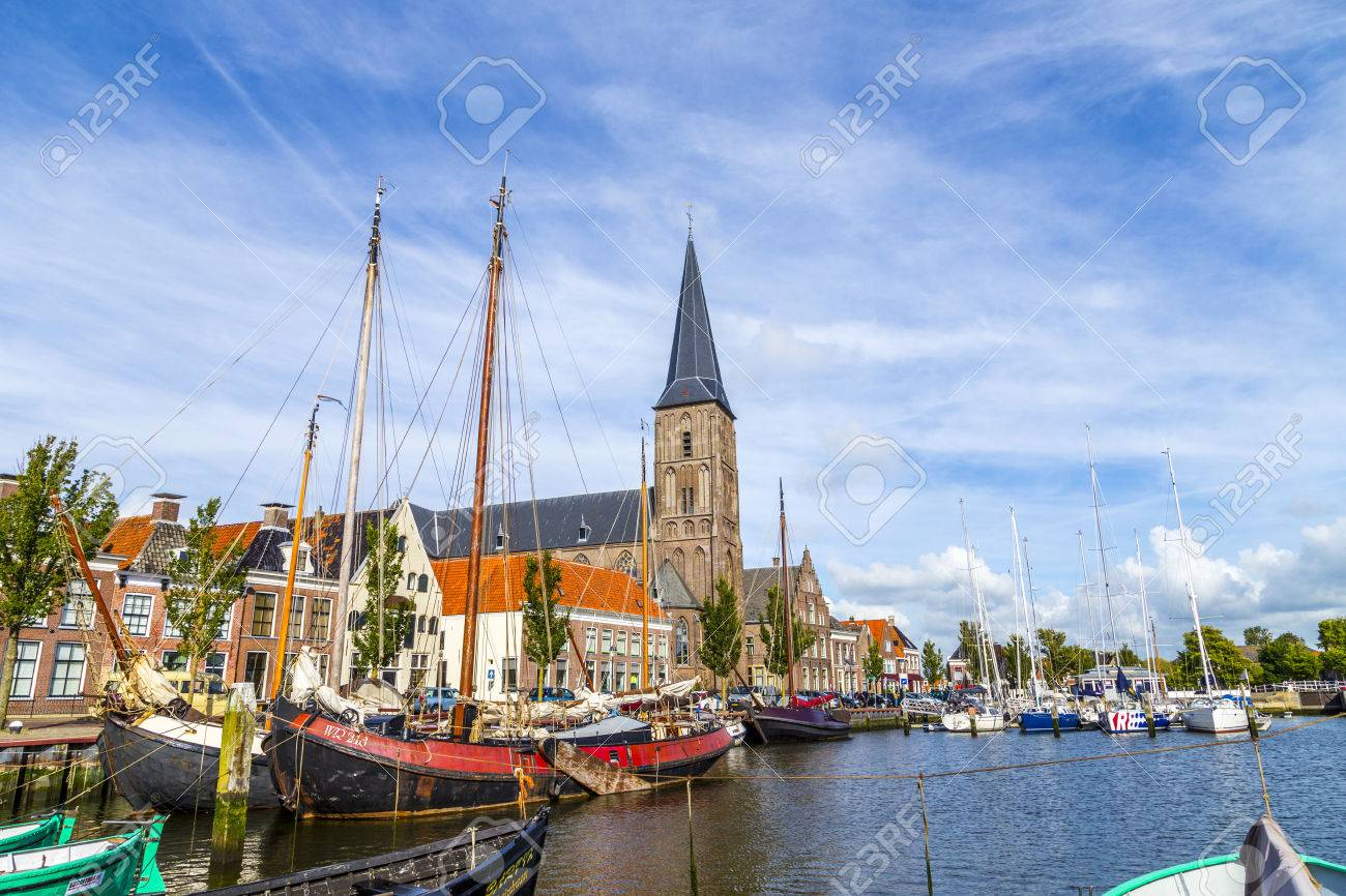 HARLINGEN, NETHERLANDS - AUG 18, 2014: pier with old boats in Harlingen, Netherlands. Harlingen became town in 1234 and is also called Venice of Netherlands. - 35782096