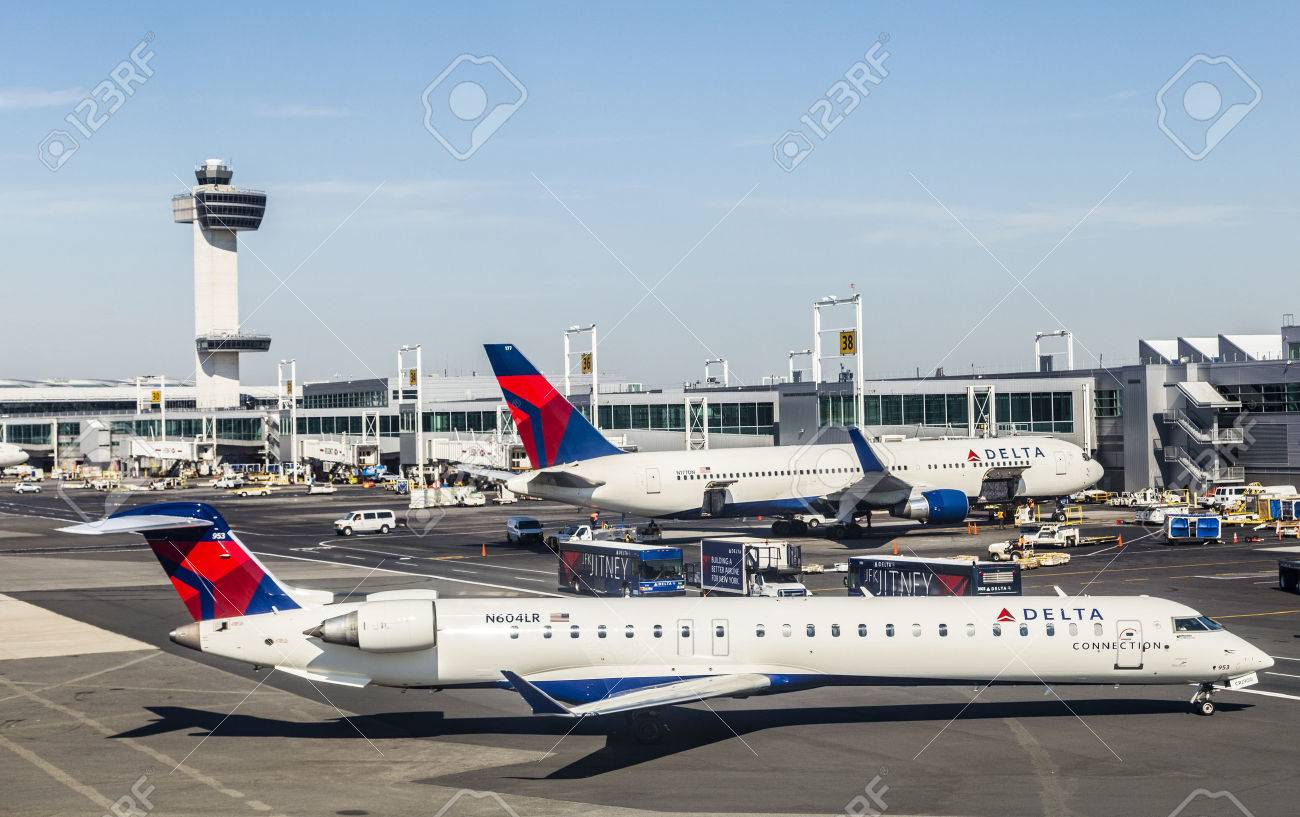 NEW YORK, USA - OCT 20, 2015: Air Traffic Control Tower and Terminal 4 with Delta Air planes at the gates in JFK Airport in NY. 1963 the airport was rededicated John F. Kennedy International Airport. - 47160680