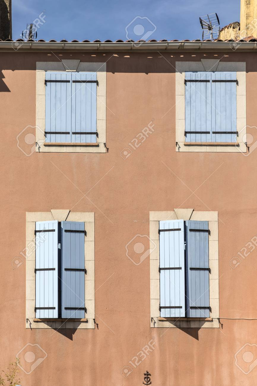 Couleurs Facades En Provence traditional french window with wooden shutters at an old house..