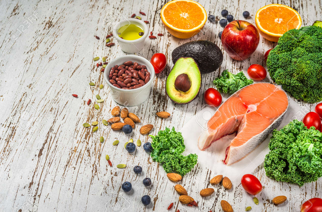 Selection of fresh fruit and vegetables, salmon, beans, and nuts. - 131290734