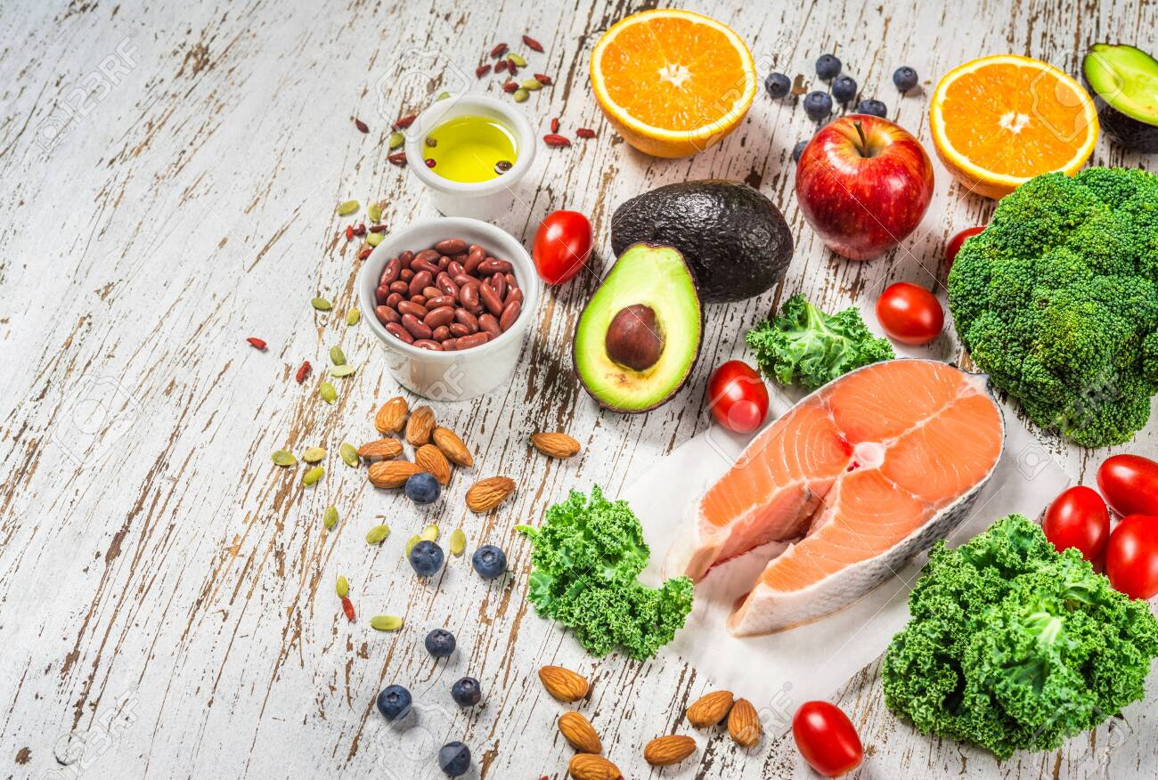Selection of fresh fruit and vegetables, salmon, beans, and nuts. - 131291477