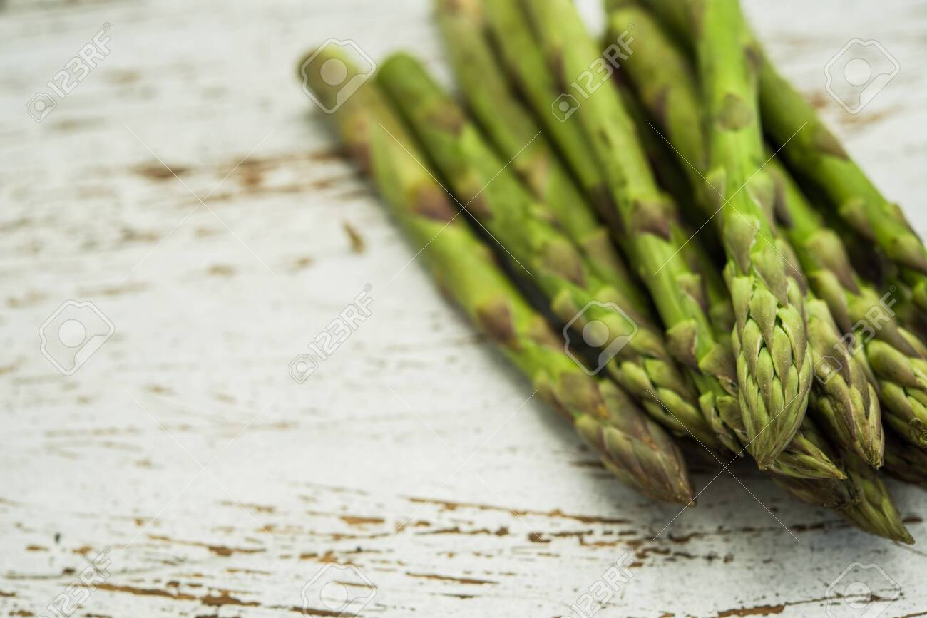 Close up of a bunch of asparagus against white wooden background. - 136358946