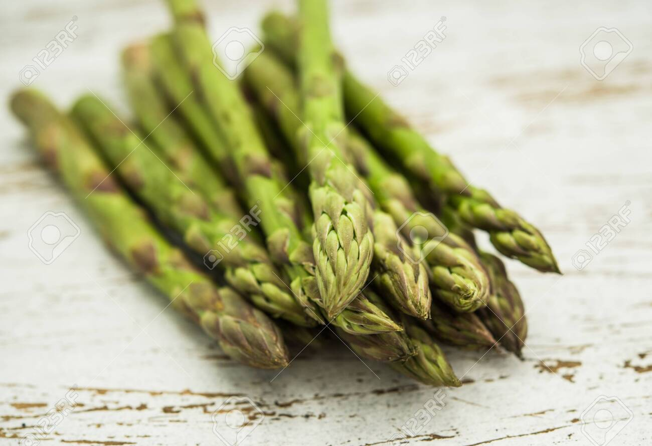 Close up of a bunch of asparagus against white wooden background - 136017361
