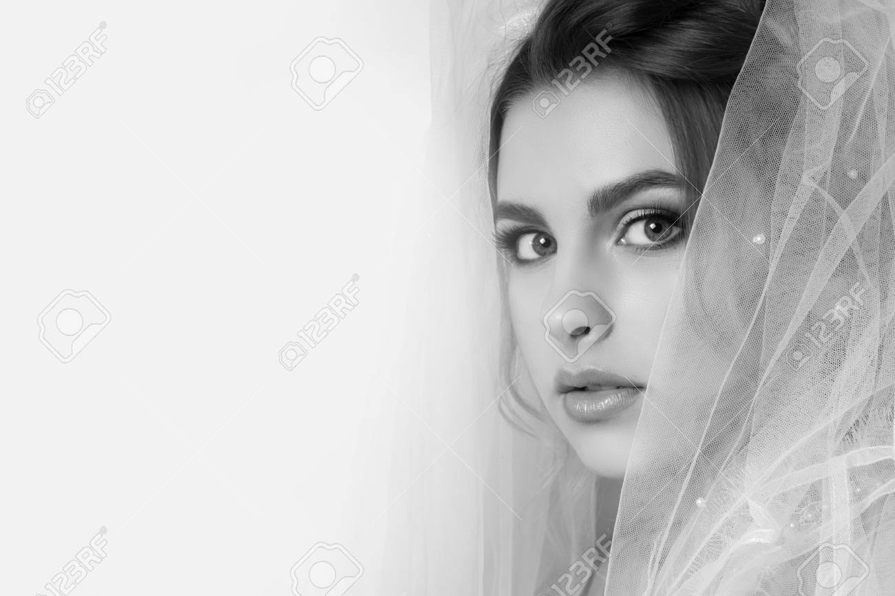 Black and white beautiful young woman bride with wedding hairstyle portrait on a light background in pastel colors