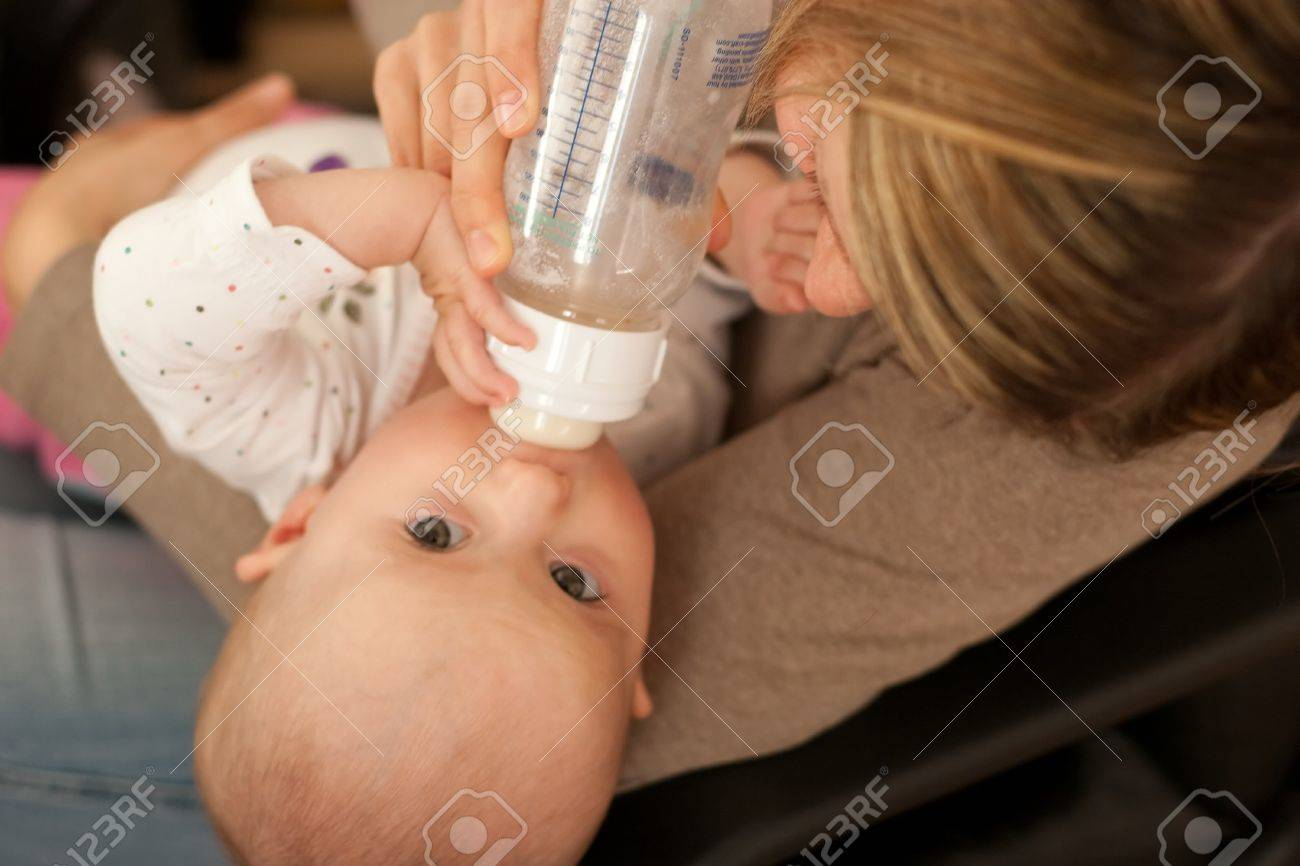 Mother feeding baby girl with bottle of milk Stock Photo - 4560949