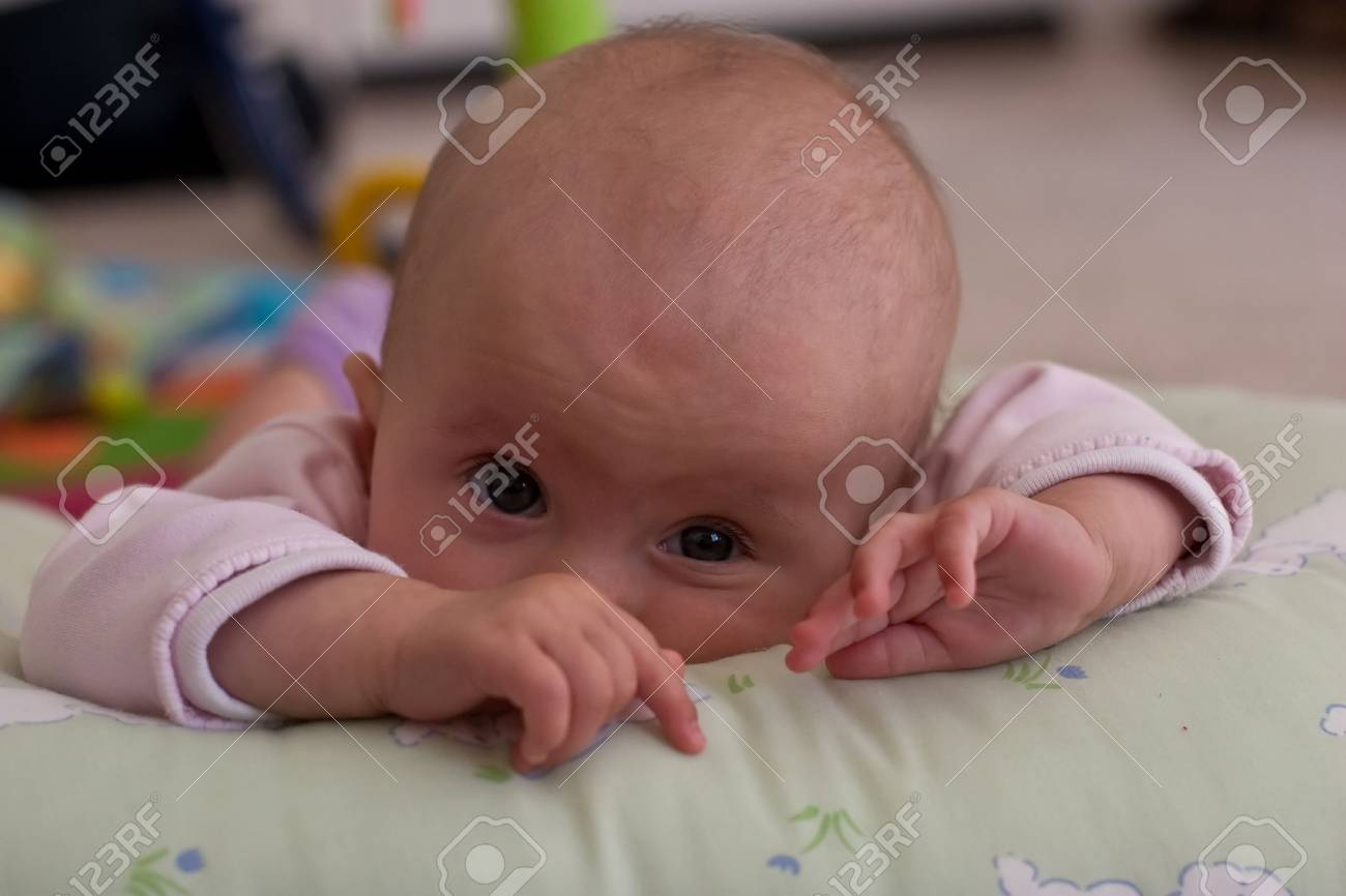 Caucasian baby girl playing on her colorful playmat. Stock Photo - 4584215