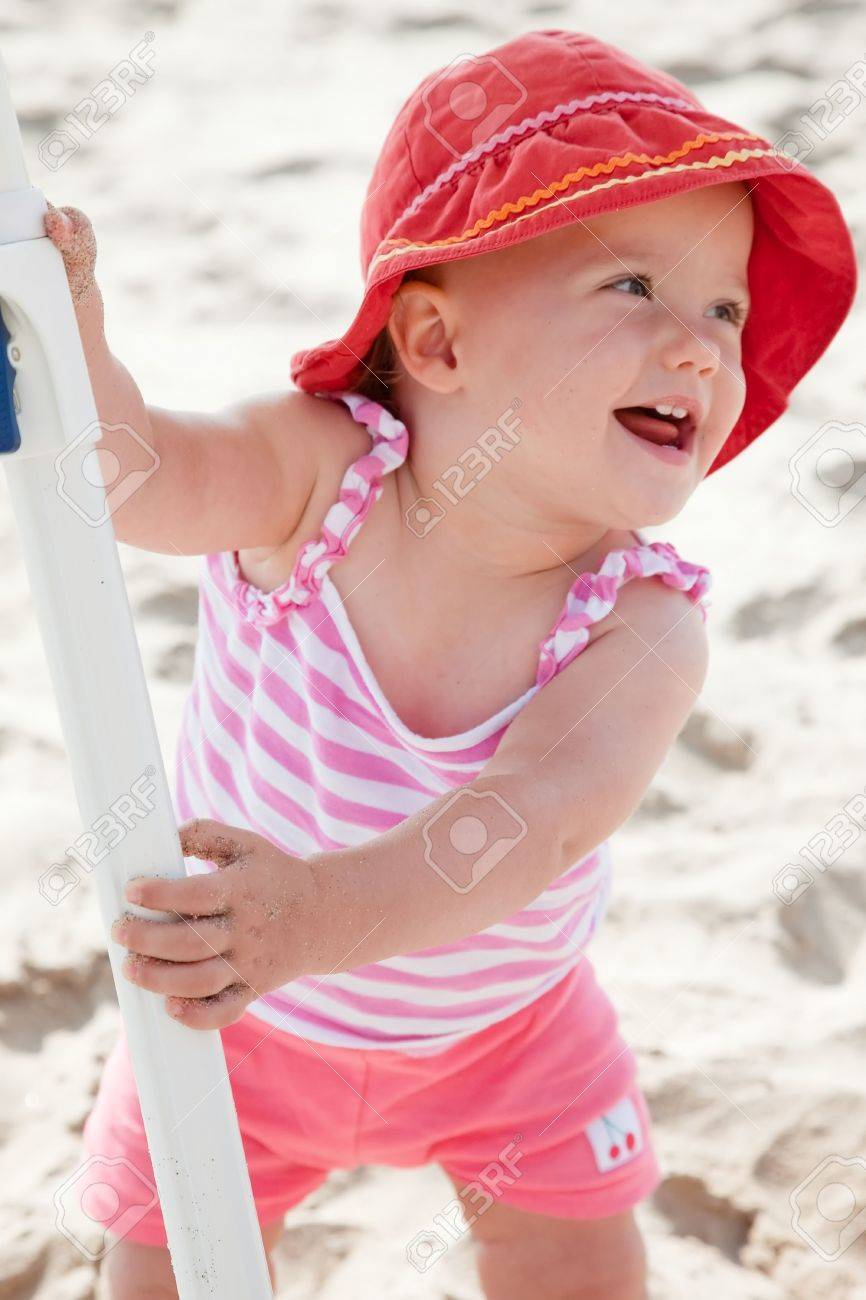 Cute Caucasian baby girl playing with the sand on the beach. Stock Photo - 5826715
