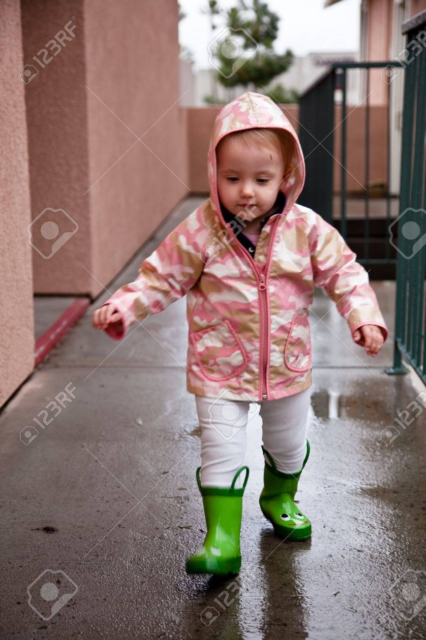 aae28685f Cute Caucasian Baby Girl Wearing Pink Raincoat And Green Rubber ...